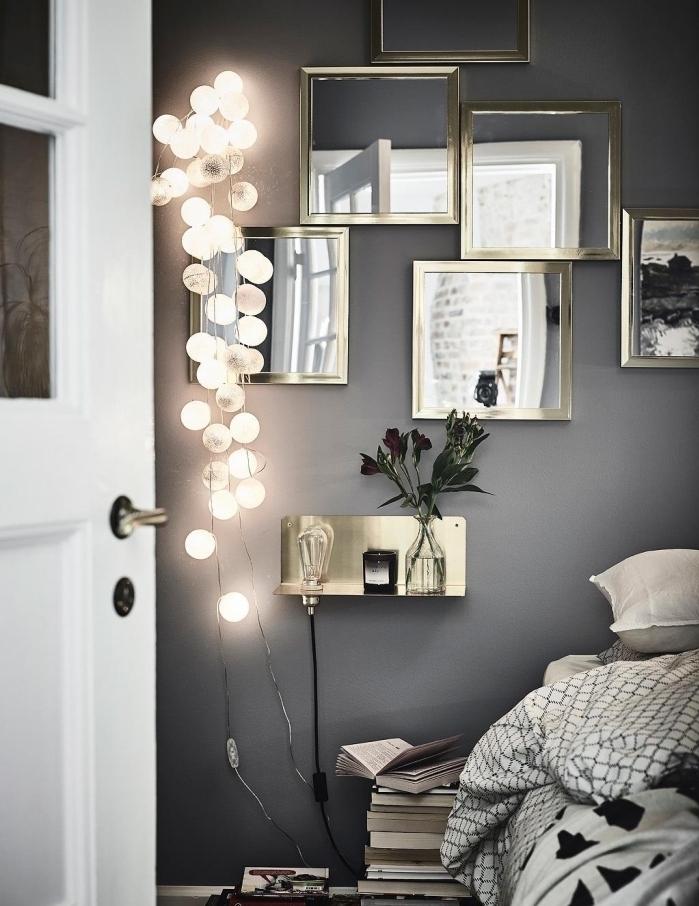 ambiance romantique dans la chambre à coucher au mur gris avec porte blanche et mur de miroir métallique