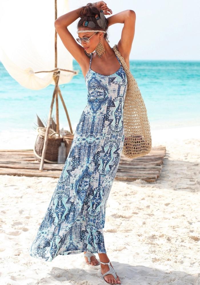vision chic de plage pour femme avec robe longue bleue et sandales argent, accessoires sac à main et boucles d'oreilles beige