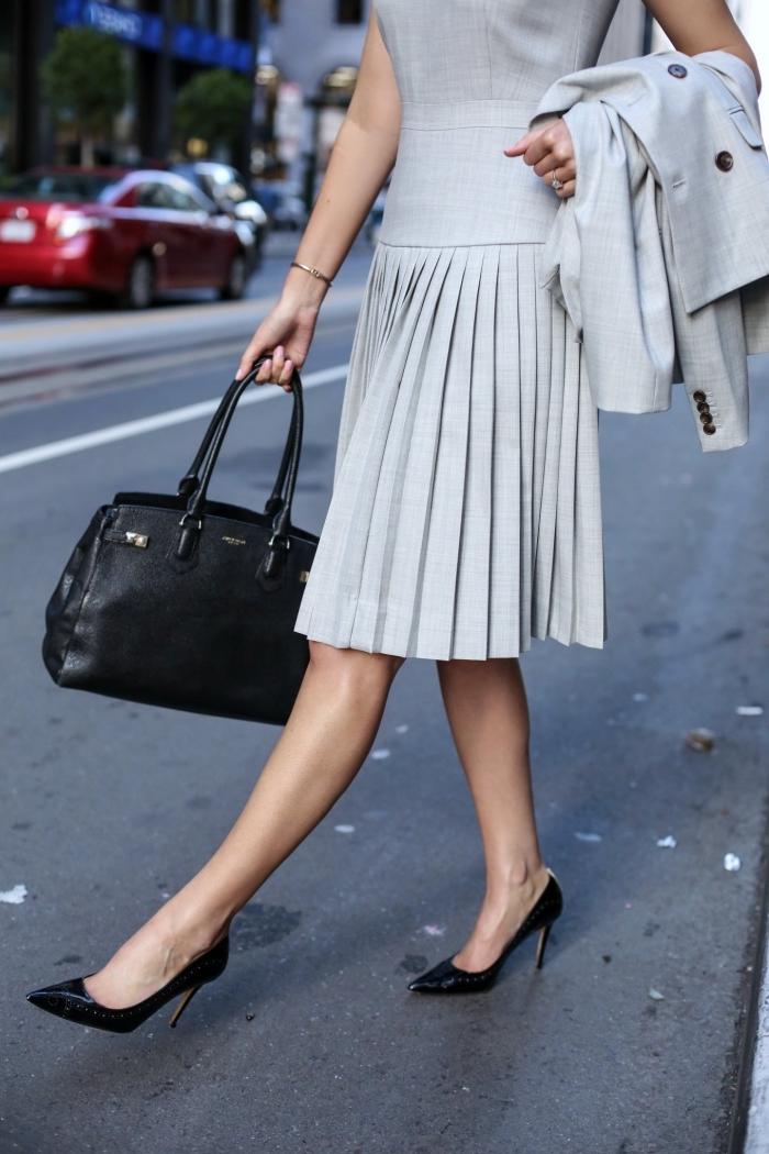 exemple de style vestimentaire femme en gris pale avec blazer gris à boutons noirs, accessoires noirs sac à main et chaussures à talons