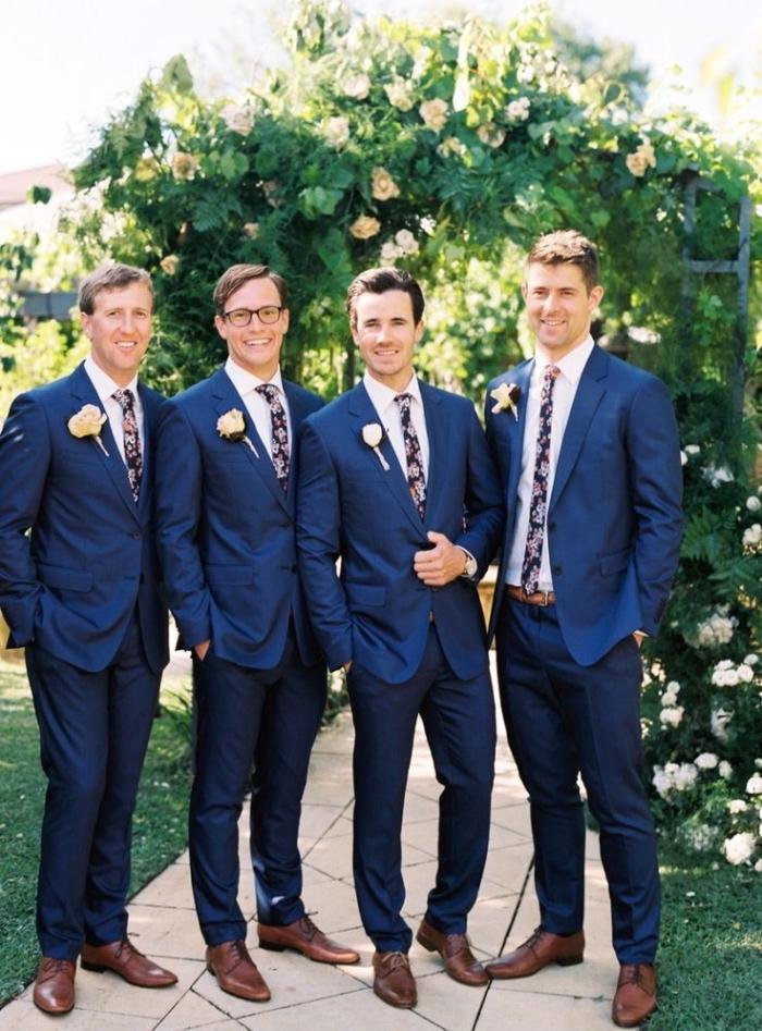 un costard mariage bleu marine classique combiné avec une cravate imprimé floral et des chaussures marron pour une vision plus moderne