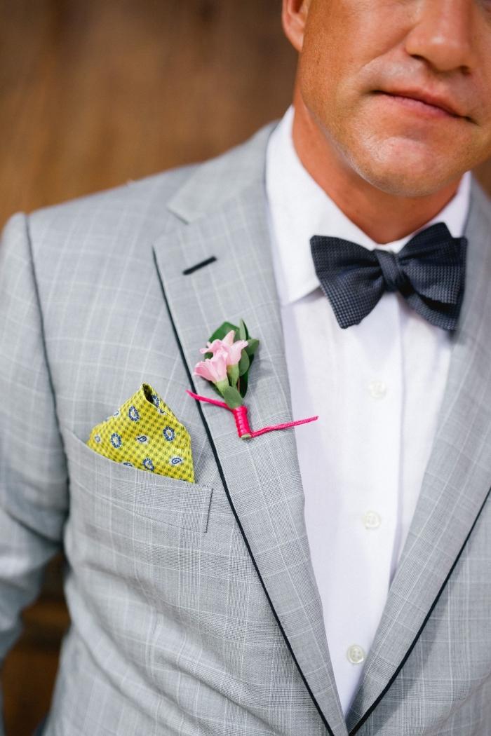 costume gris clair à carreaux subtils avec des revers à bords noir, dynamisé par une pochette jaune imprimé