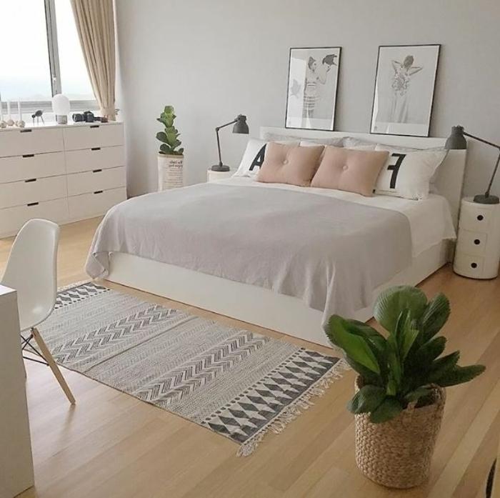 chambre à coucher scandinave, carpette ethnique, lit en blanc et gris, sol en lattes de bois, peintures encadrées