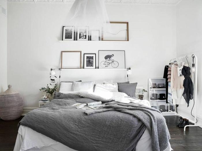 chambre à coucher adulte moderne style scandinave, sol en bois foncé, porte-vêtement blanc, peintures et photos monochromes