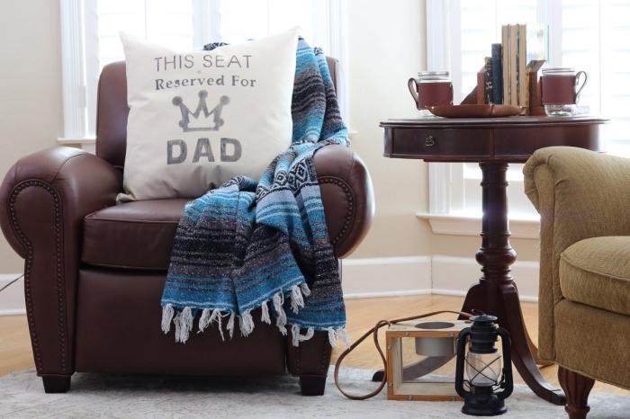 exemple de coin homme dans une pièce beige au plancher de bois aménagé avec un coussin personnalisé à mot papa