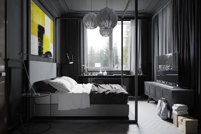 décor foncé dans la chambre adulte aux murs gris foncé et plancher de bois peint en gris clair avec peinture jaune