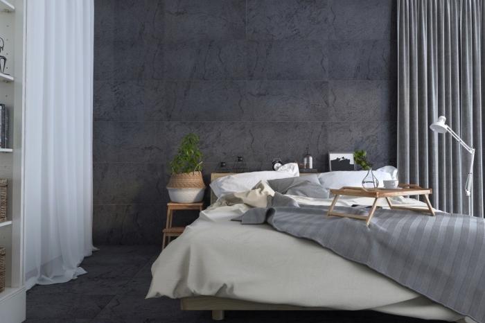 ambiance cozy dans l'esprit scandinave dans une chambre à coucher aux murs gris avec rideaux blancs et meubles en bois