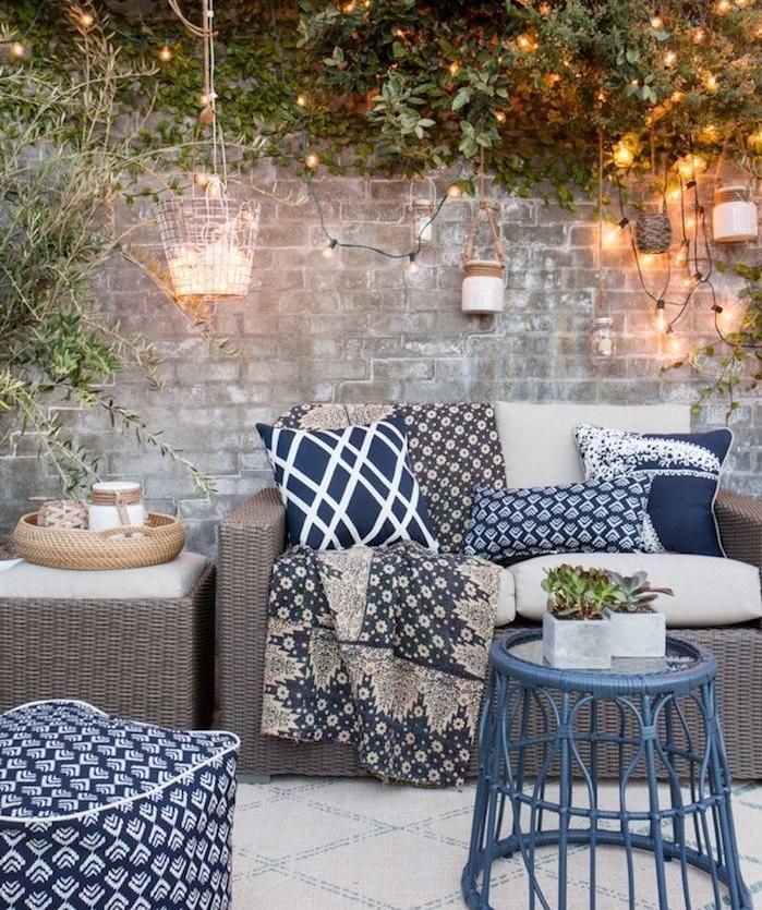 idée d aménagement cour extérieur avec table de service et canapé en rotin, table modele intéressant, mur de pierre et guirlande lumineuse exterieure deco
