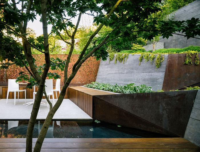 coin repos et ropas en table et chaises blanches, bassin d eau et terrasse en pente, chemin en bois composite, plantes orientales