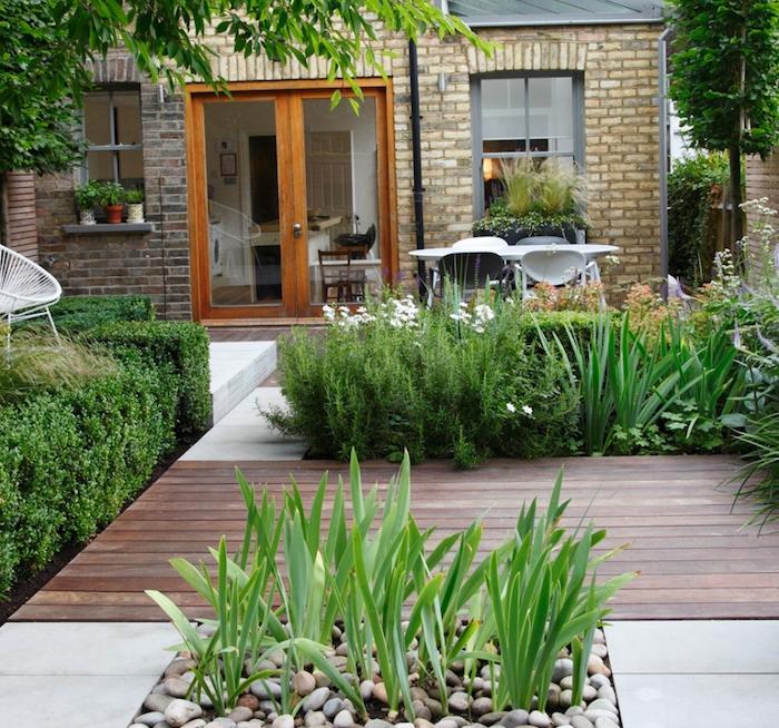 terrasse maison en bois et dalles avec plusieurs espèces végétaux, buis, arbustes, fleurs, coin repas, maison e pierre