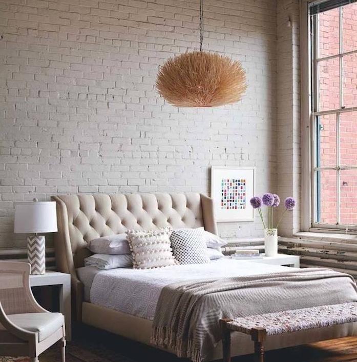 mur de briques blanches, linge de lit gris, beig et blanc, tete de lit capitonnée, suspension originale, parquet bois, grandes fenêtres