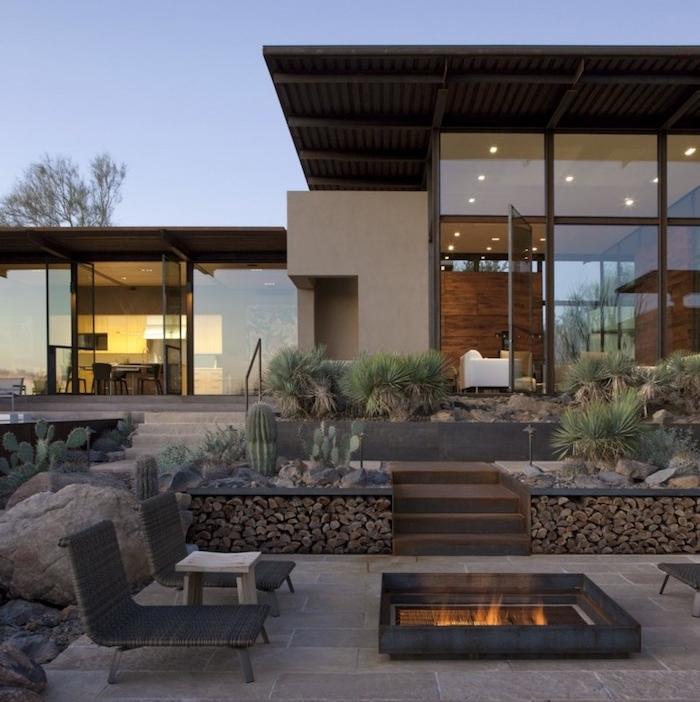exemple d aménagement extérieur en dalles de béton, chaise longue rotin, brasero moderne, plantes cactus, maison moderne