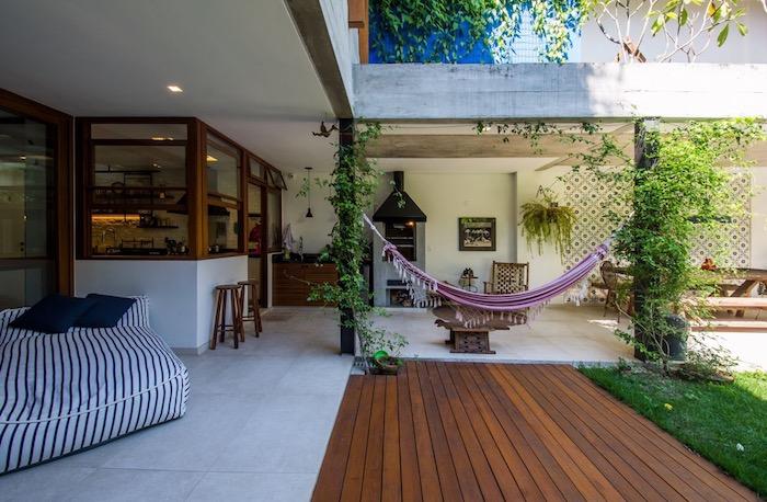 deco terrasse exotique avec revetement en dalles et bois composite, matelas noir et blanc, hamac, gazon vert