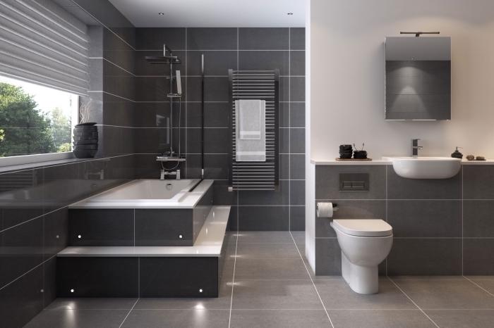modèle de salle de bain moderne avec murs en revêtement carrelage gris et plafond blanc avec éclairage led