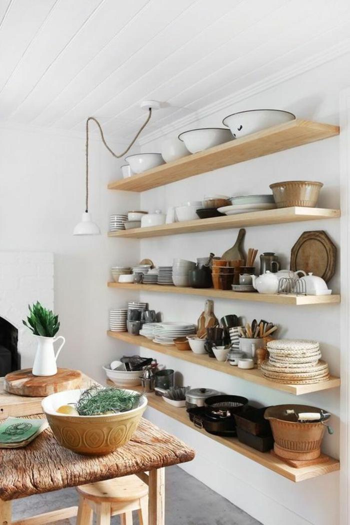 amenagement de placard, rangement tiroir, etagere cuisine en bois clair, mur et plafond blancs, sol recouvert de carrelage gris, table en bois en style rustique, petit luminaire en métal blanc suspendu sur un fil noir long