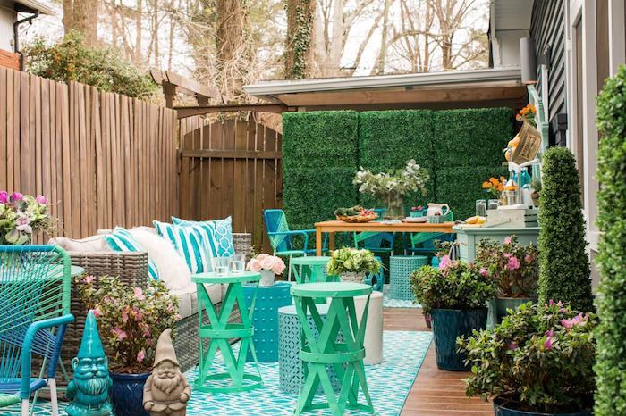 amenagement terrasse exterieure, un salon de jardin composé d un canapé cocooning, plusieurs tables basses rondes, nains de jardin, cloture bois, mur végétal extérieur, tapis bleu, coin repas à côté