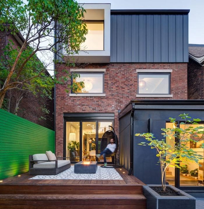 idée terrasse bois composite, munie d un tapis gris et blanc, canapé bois, table basse et fauteuil balançoire, maison moderne