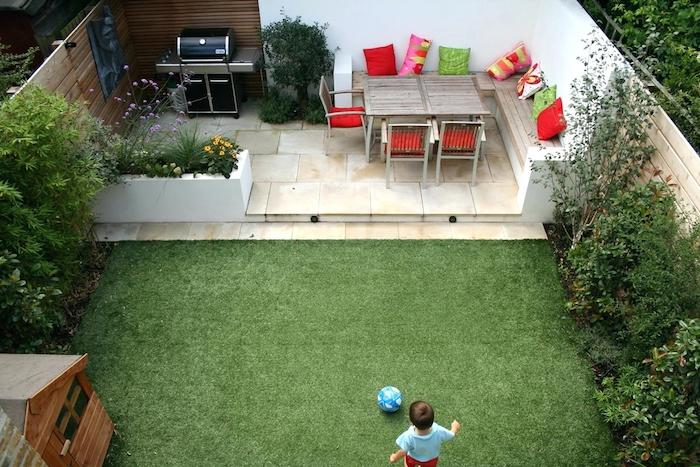 aménagement cour extérieur avec une terrasse en carrelage, banc bois et méton, chaises métalliques, barbecue, gazon et bordure de végétaux