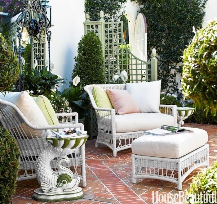 pavage exterieur avec canapés et table basse en rotin tressé, plusieurs buis taillés, style maison vintage