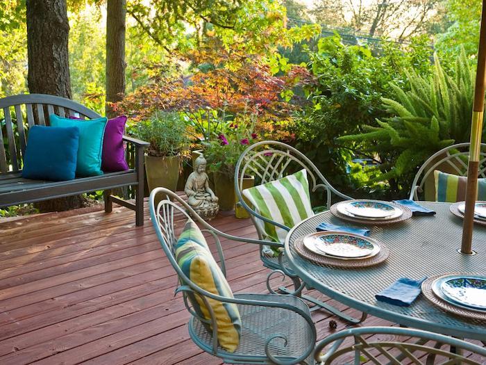 deco terrasse orientale avec coin repas de table et chaises metalliques, revetement sol en composite, banc en bois, statuette bouddha