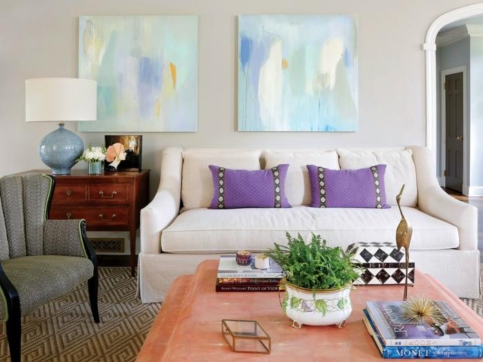 grand pouf couleur corail, coussins lilas sur un canapé gris clair, commode en bois ancienne, chaise grise