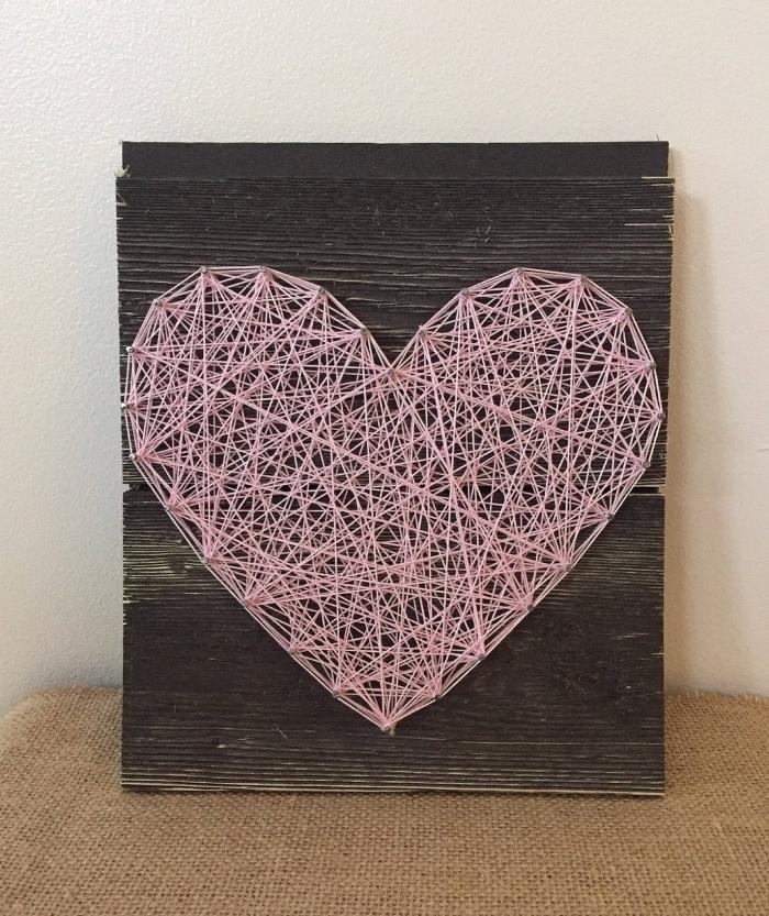 modèle de décoration murale fait main avec panneau de bois foncé et fil rose en forme de grand coeur DIY