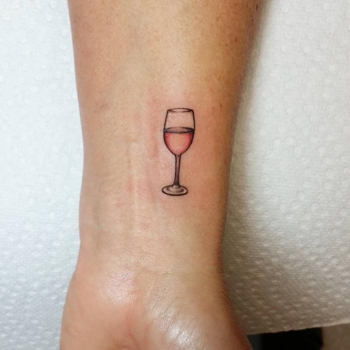 modèle de petit tatouage sur le poignet à design verre de vin rosé, idée dessin en encre pour femme qui aime le vin
