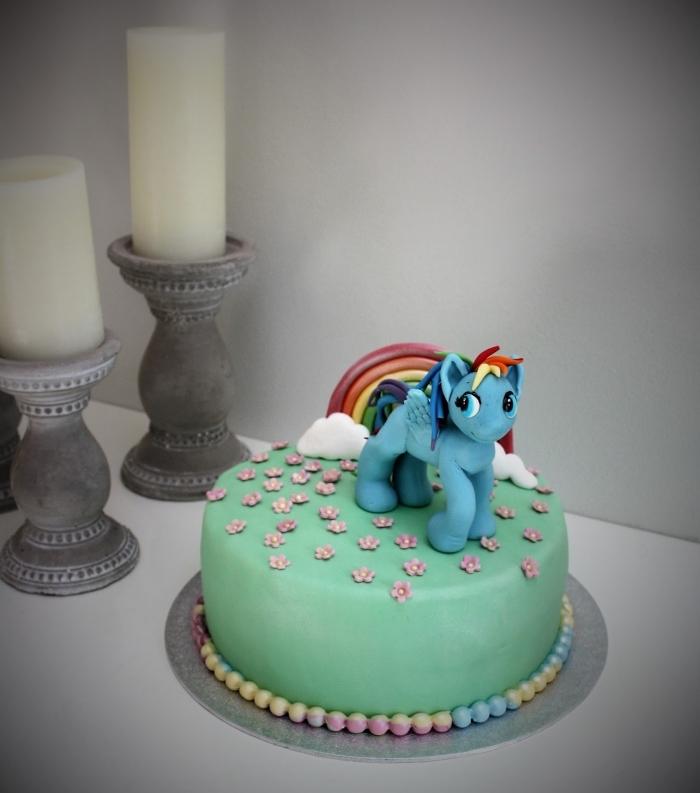 décoration originale de gateau cake licorne magique recouvert de pâte à sucre vert, décoré avec de petite fleurs et une figurine de licorne modelée en pâte à sucre