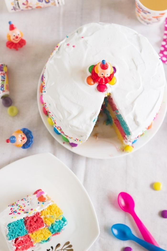 idée originale pour un gâteau arc en ciel damier au glaçage de chantilly décoré avec des figurines de clown