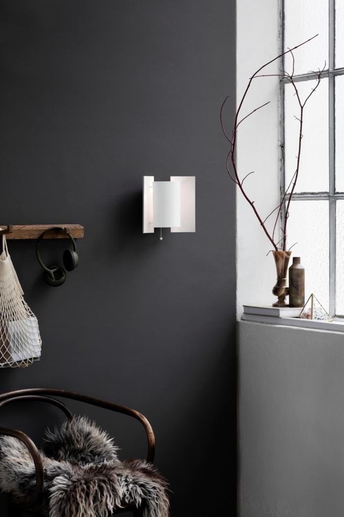 aménagement coin de repos dans une chambre aux murs anthracite avec étagère en bois massif et vase marron