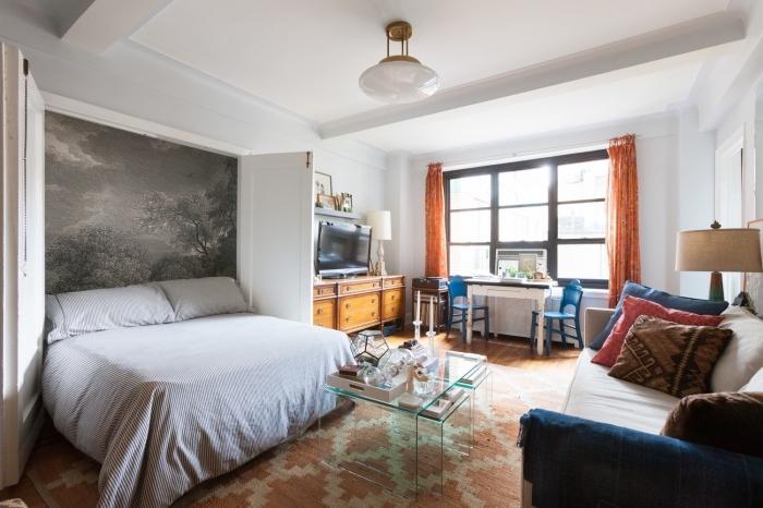 idée d'aménagement fonctionnel et déco d'un petit studio avec une tete de lit papier peint imprimé qui délimite la niche murale du lit escamotable
