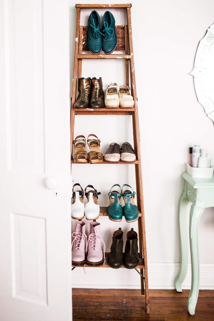 une échelle vintage détournée en meuble pour chaussures fonctionnel et esthétique, posé contre le mur à côté de la coiffeuse dans la chambre à coucher