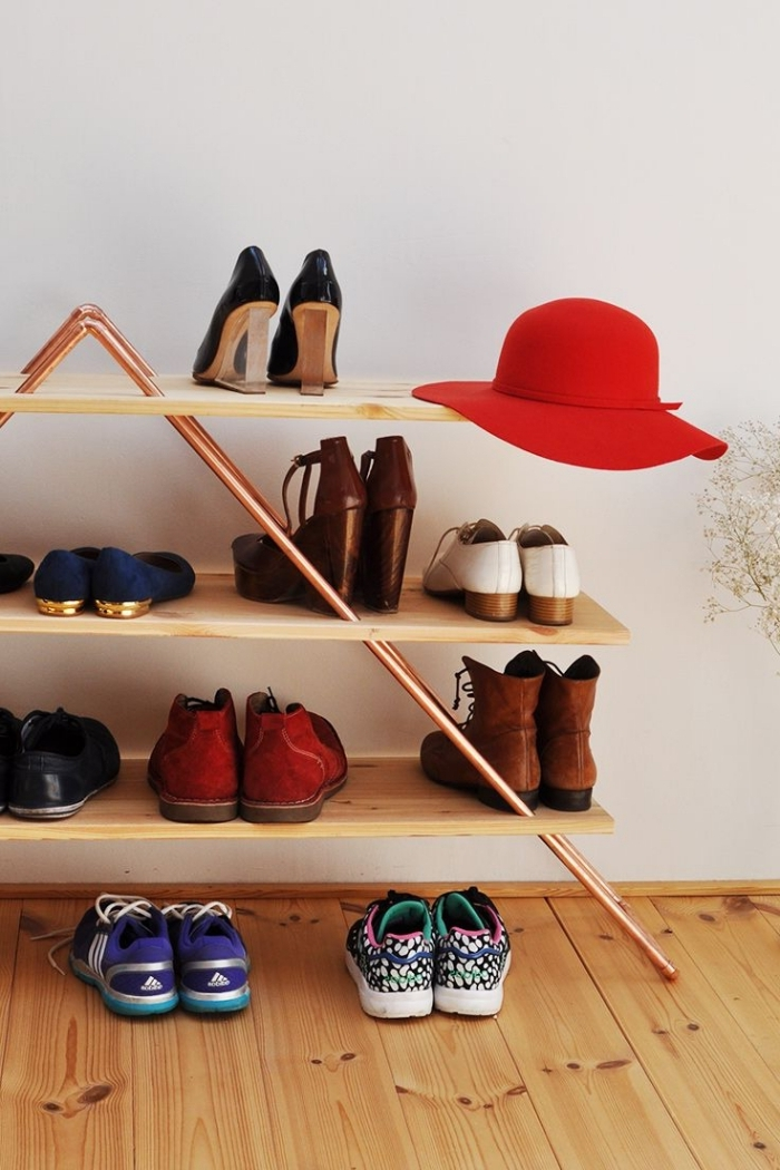 idée de meuble pour chaussures à fabriquer soi-même réalisé avec des planches de bois et des tuyaux en cuivre, au design géométrique