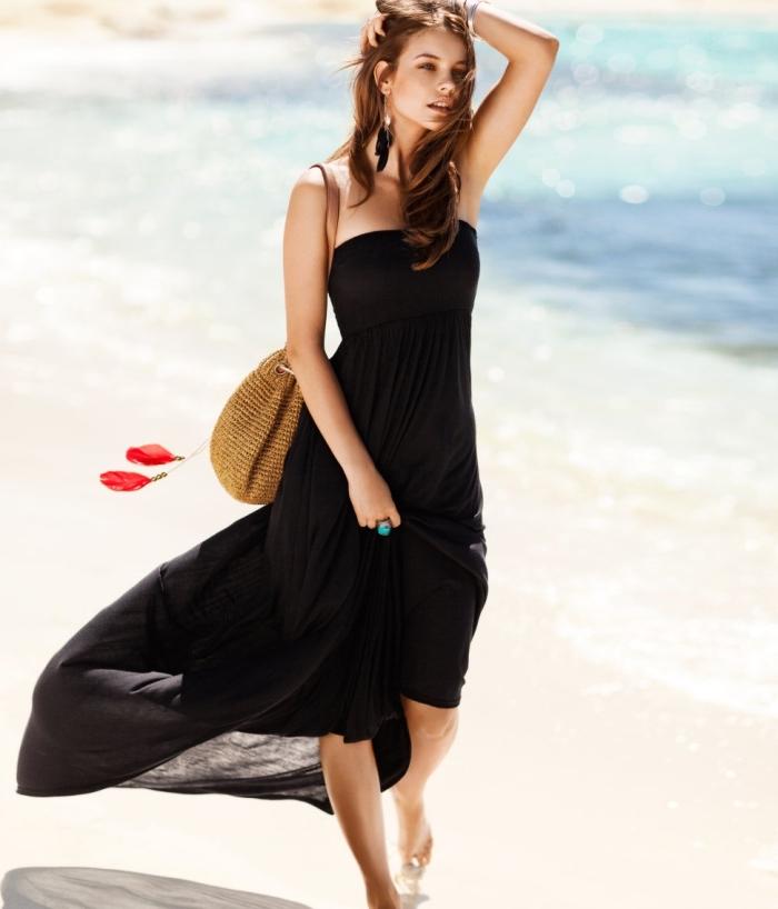 modèle de robe plage longue avec bustier de couleur noire combinée avec sac a main en paille et boucles d'oreilles plumes