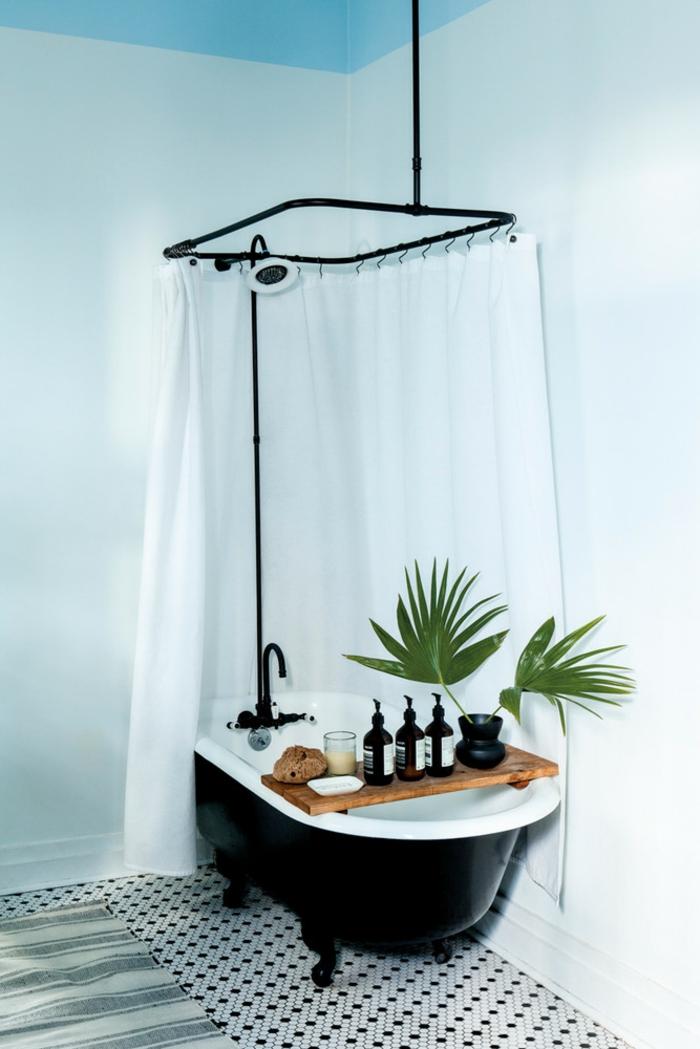 baignoire en noir et blanc, carrelage vintage en noir et blanc style années 50, tapis aux rayures vert et réséda horizontales, plante qui absorbe l'humidité, rideau douche et baignoire en blanc