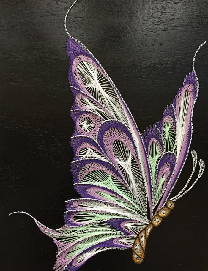 loisirs créatifs avec une technique de fabrication créations jolies en fil, modèle de papillon 3D sur planche de bois noire