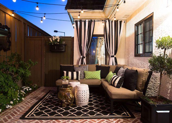 pavage exterieur sur une terrasse exterieure, tapis noir et blanc, canapé bois avec coussins d assise marron, guirlande lumineuse exterieure