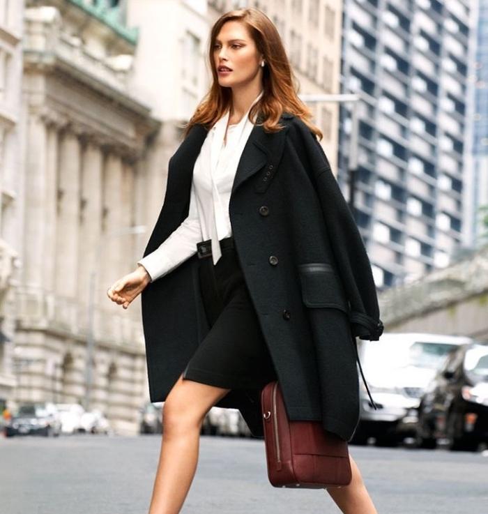 look business femme avec jupe noire et chemise blanche combinés avec manteau noir loose et sac à main marron