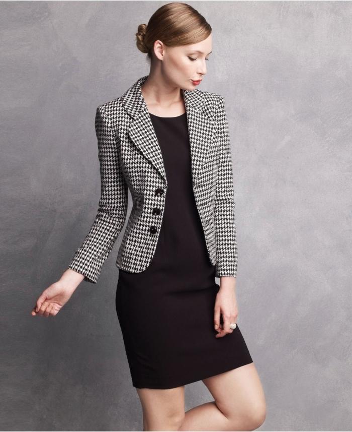 look professionnel aux cheveux propres et attachés en bun, modèle de robe mi-longue noire combinée avec blazer rayée
