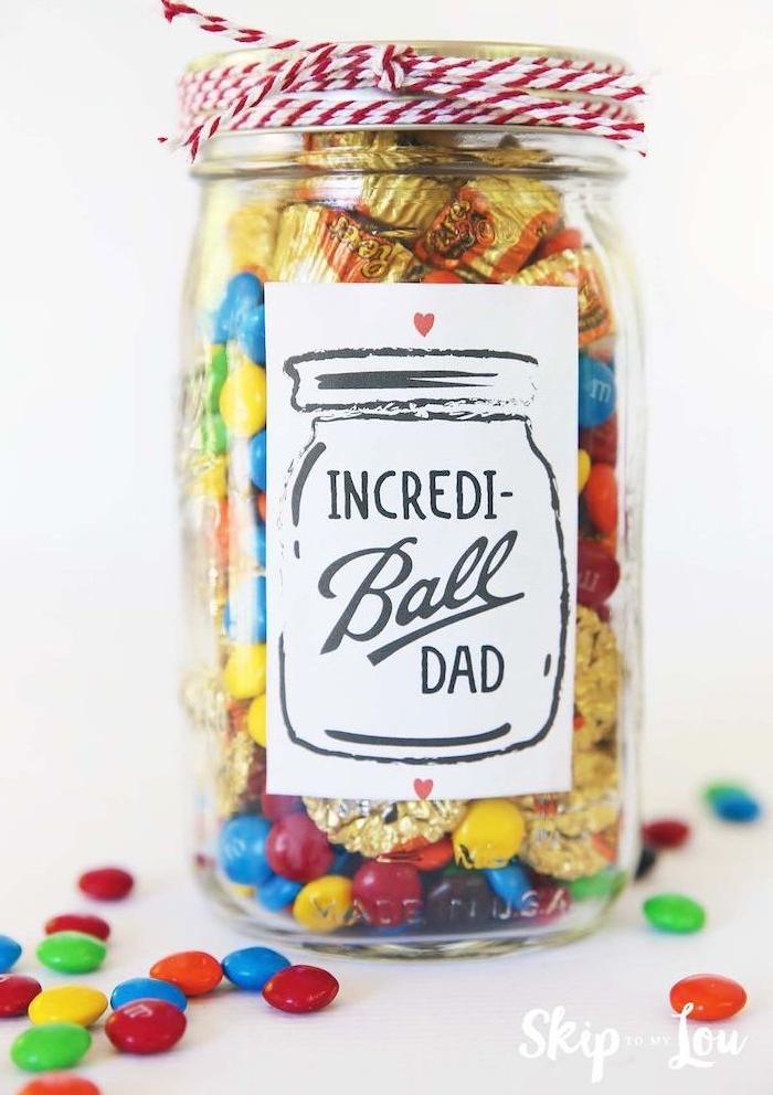 bocal en verre rempli de bonbons et autres gourmandises, couvercle décoré de fil rouge et blanc, idees cadeaux fete des peres
