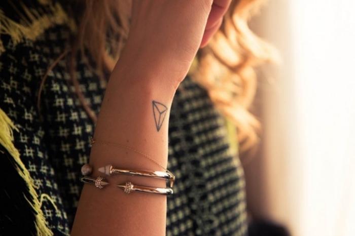 joli mini tattoo discret aux lignes simples et design géométrique réalisé sur le poignet d'une femme aux cheveux longs blonds