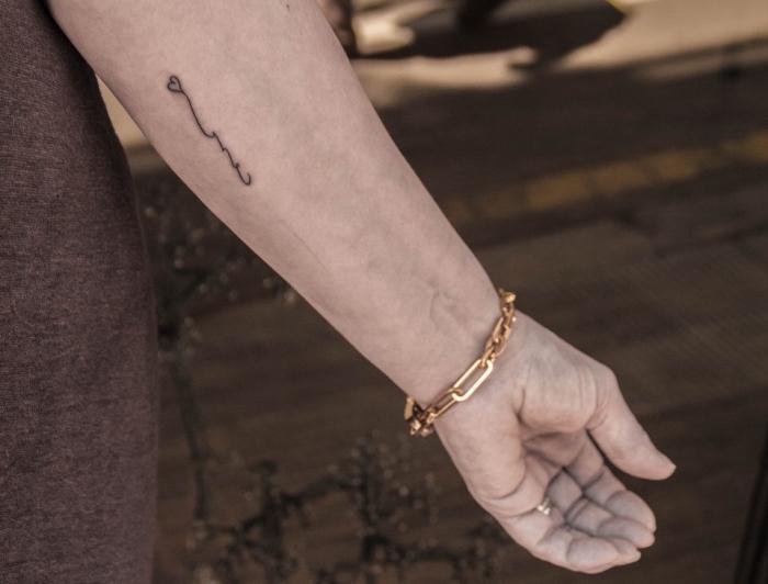 idée tatouage femme sur la main, dessin en encre dans le style minimaliste avec un petit coeur sur la main féminine
