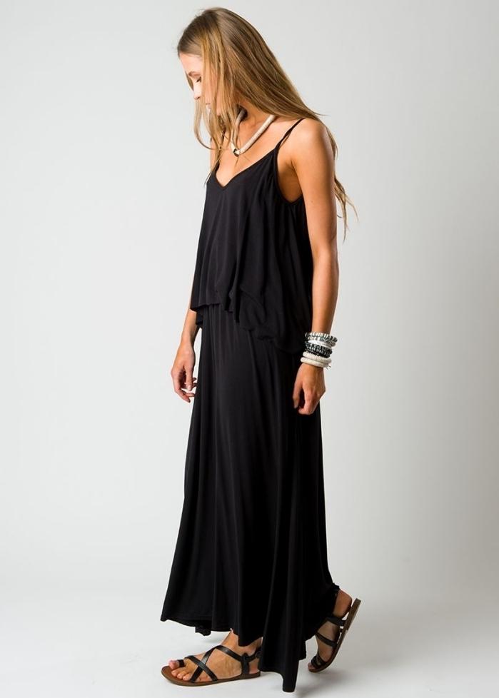 modèle de robe longue noire de style hippie chic combinée avec sandales plates noires et accessoires bracelet et collier
