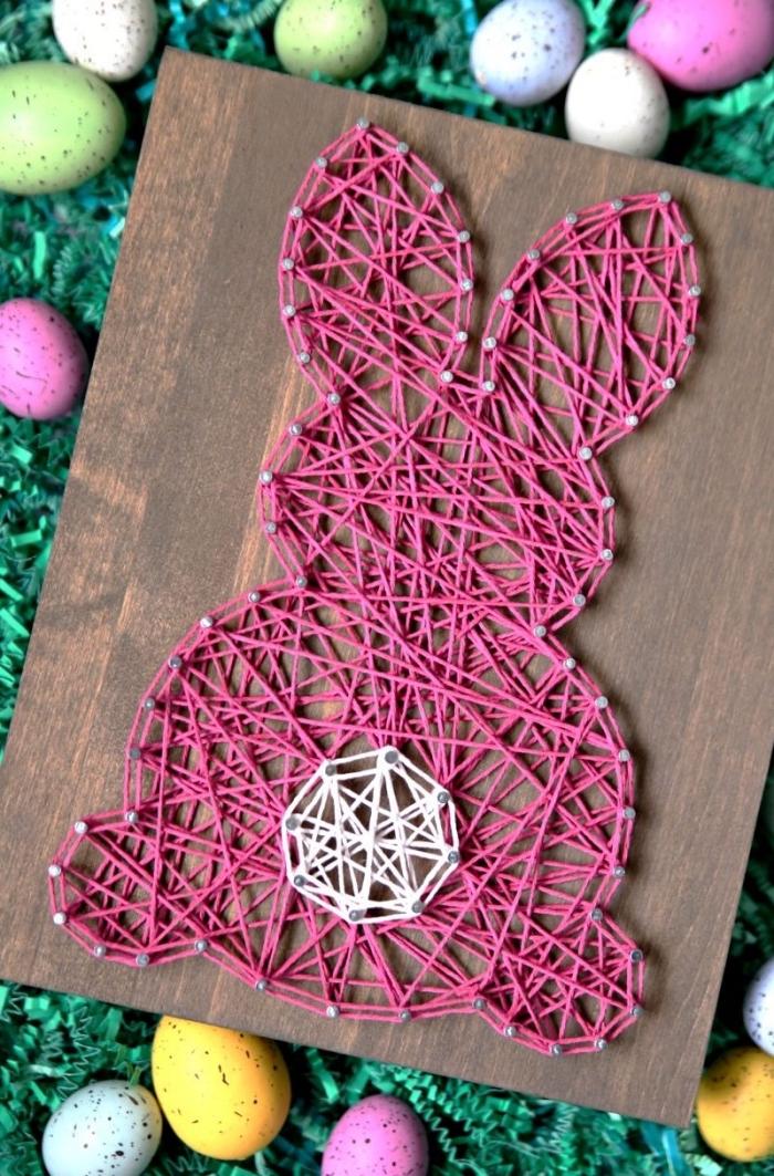 quelle déco de Pâques réaliser avec les enfants, modèle de tableau de bois foncé décoré de fil rose et blanc en forme de lapin