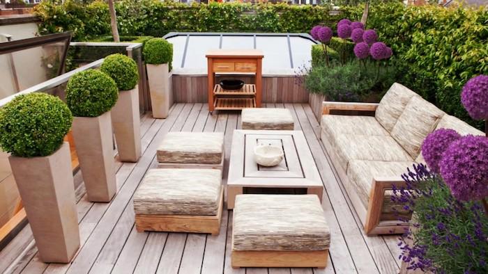 exemple d aménagement extérieur de terrasse en bois composite, canapé, tabourets, table bois et coussins d assise gris et beige, buis taillé, fleurs