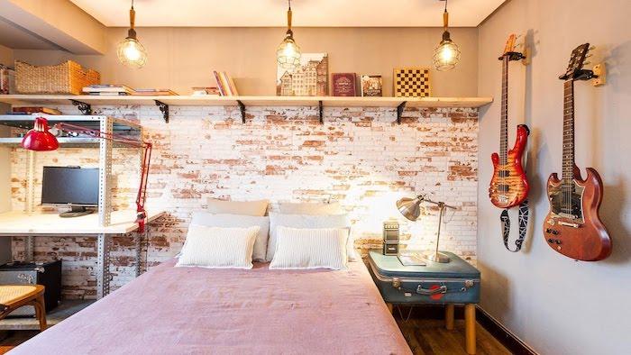 mur de briques avec une étagère bois, linge de lit blanc et rose, bureau style industriel et guitares décoratives, table de nuit en malle recyclée