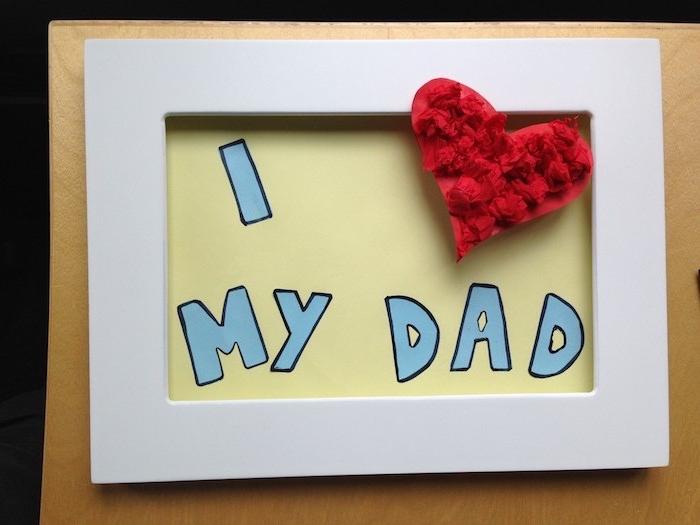 cadre photo blanc avec un fond décoré lettres j aime papa et un coeur en papier de soie rouge, activité fete des peres