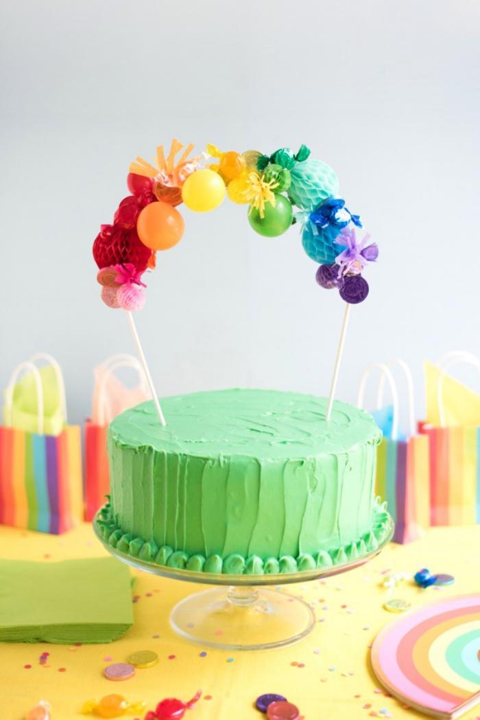 comment décorer un gateau arc-en-ciel, un cake au glaçage vert surmonté d'un cake topper personnalisé avec des boules en papier