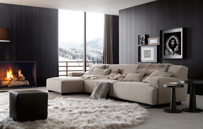 déco chaleureuse et comfortable dans un salon aux murs foncés avec cheminée et canapé d'angle beige, modèle de tapis en fausse fourrure blanche