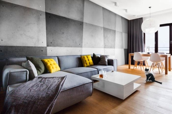 décoration murale avec peinture en différentes nuances de gris à design géométrique, aménagement avec canapé d'angle gris et coussins jaunes