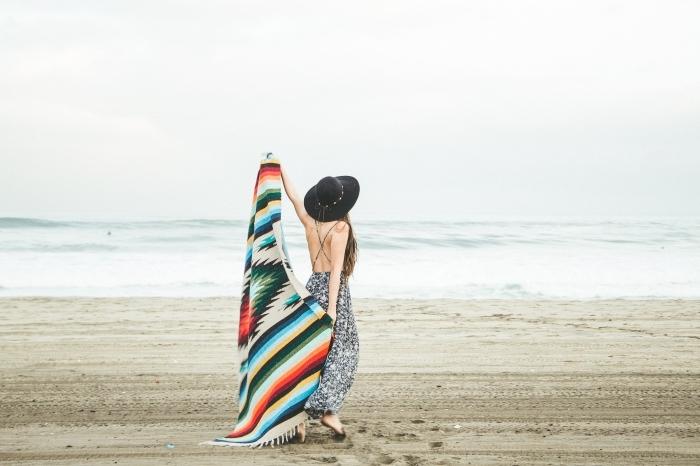 accessoires à combiner avec une robe longue, capeline noire et serviette de plage bohème avec frange multicolore
